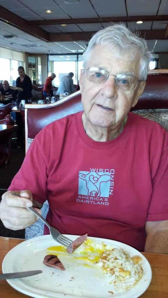 90 year old man with gray hair and glasses eating breakfast of eggs and sausage at a restaurant looking at the camera