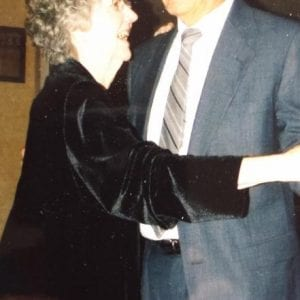 gray haired woman in black dress dancing with her gray haired husband in a gray suit