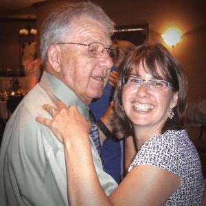 Daughter and father dancing and smiling at the camera
