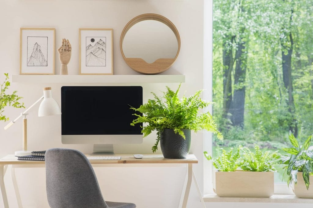 Grey chair at desk with plant in bright home office interior with window and posters. Real photo